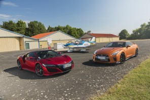Honda NSX rouge vs Nissan GT-R orange devant un avion