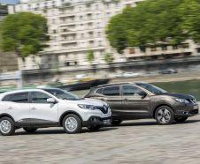 Renault Kadjar 2015 Zen blanc et Nissan Qashqai Connect Edition marron roulant cote a cote sur une route pav�e